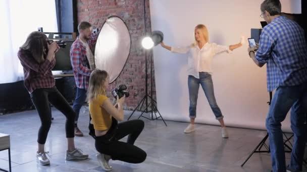 Modeprofis mit Slr-Kameras schießen Fotos während eines Seminars für Fotografen im Fotostudio mit Model