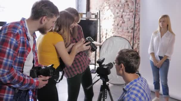 photo workshop, company of photographers discuss installation of SLR camera during training of professional studio