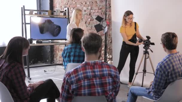 photographer talks about device of a DSLR camera to young creative people at a photo seminar in professional studio on background of TV with picture of equipment