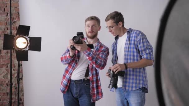 Profifotografen mit Spiegelreflexkameras in der Hand diskutieren während des Fotoshootings im Studio über Modefotografie