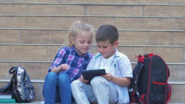 modern gyermekkor, a hátizsákos tanulók digitális táblagépet használnak az iskola lépcsőjén ülve a szabadtéri szünetben