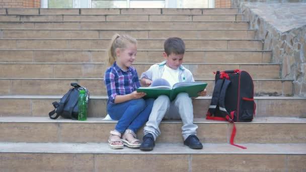 školní přátelství, spolužáci s batohy sedí na schodech a recenzi knihy během přestávky na čerstvém vzduchu