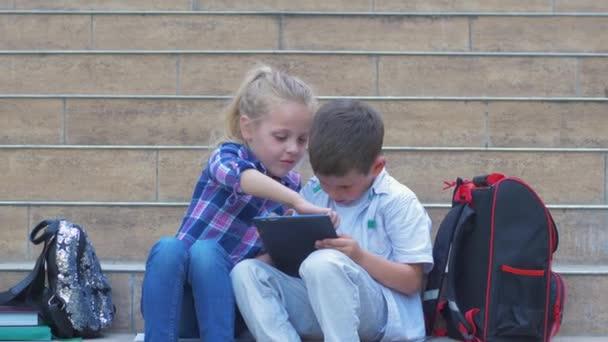 školáci používají digitální tablet posazený na schodech s batohy během přestávky pod širým nebem