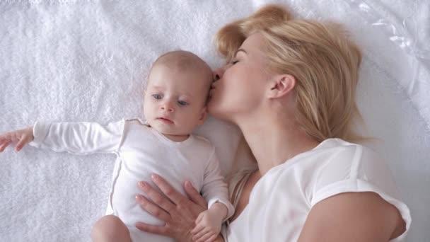 Nejlepší okamžiky života, milování šťastné mladé matky objetí a polibky novorozené dcery na přikrývce a pohled na kameru
