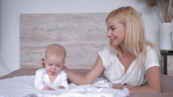 lásku a štěstí, mladá matka s novorozence tráví čas pohromadě a leží na posteli a doma se dívat na kameru