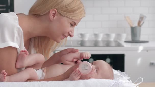 caring mother gives to drink water from the bottle to her newborn girl on changing table on kitchen then kisses hands of little baby