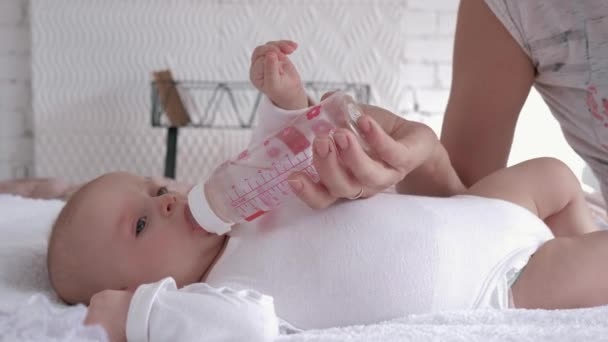 mother care, newborn baby girl is lying on the bed and drinking water from a bottle that parent holds in her hands