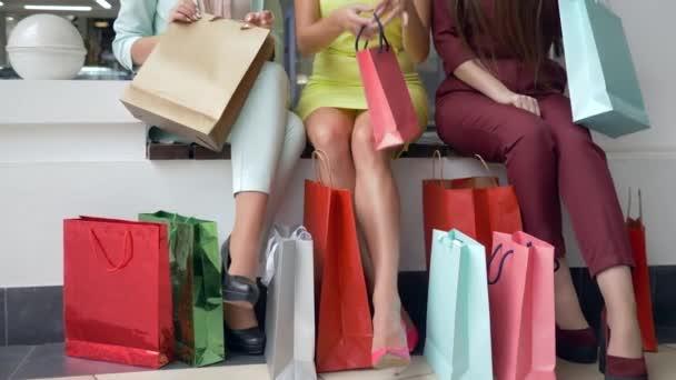 shopaholic dívky sledují nové nákupy v sezóně slev a prodeje a hodně světlé nákupní tašky v blízkosti nohou