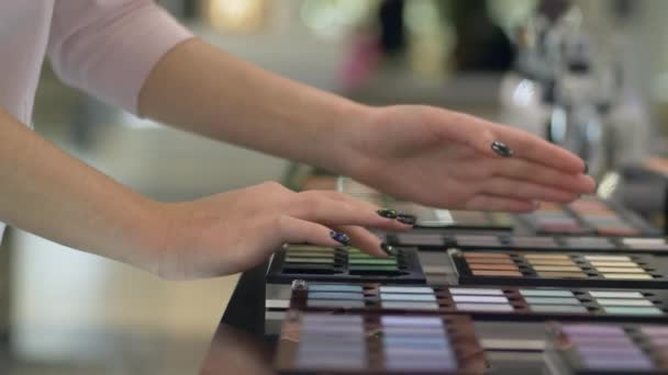 cosmetic shop, buyer woman select eyeshadow from palette of different colors for bright makeup and Apply cosmetics testing on arm at store