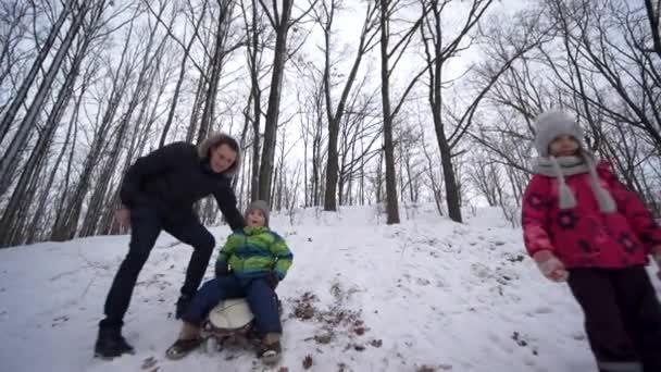 Familien-Winteraktivitäten, Junge auf Rodelausfahrten vom verschneiten Hügel im Wald