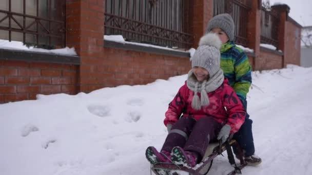 Winterunterhaltung, kleine Jungen und Mädchen fahren auf dem Schlitten auf einer verschneiten Straße