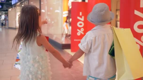 big discounts, Fashionable children go past shop windows with dummies after purchases on expensive boutiques in mall, text appears in an clip last days of sale