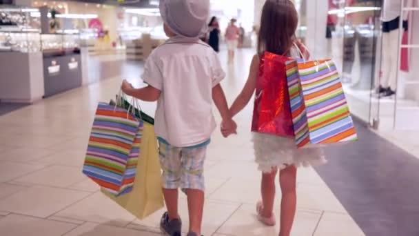 vásárlási nap, divatos kislány barátjával sok csomag séta együtt a plázában vásárlás után