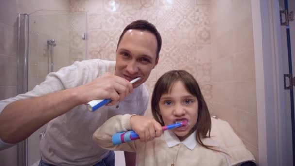 oral health, happy father with child girl with toothbrush brushing teeth in front of mirror