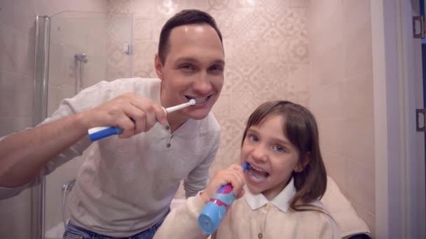 ústní hygiena, radostný táta s dcerou s kartáčkem na zuby před zrcadlem
