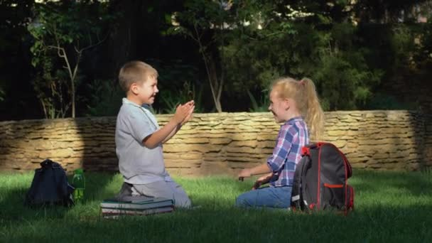 cheerful schoolboy and schoolgirl playing clapping game sitting in park after teaching on school break