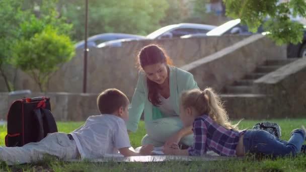 vidám nő pedagógus olvasni könyvet a kisfiú és a lány ül a zöld fű a természetben napsütésben iskola után