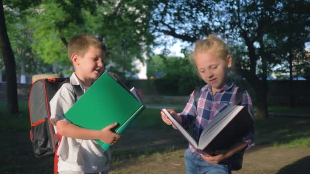children education, schoolchildren boy and girl with books in hands read after lessons standing in park