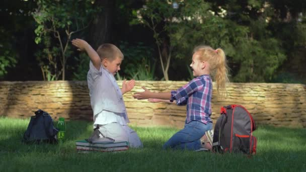 educational games, scholar girl and boy playing clapping game sitting on lawn after schooling on school break
