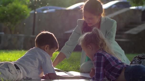 óvodai oktatás, gyönyörű női olvasókönyv a kisfiú és a lány ül a zöld fű szabadban napsütésben