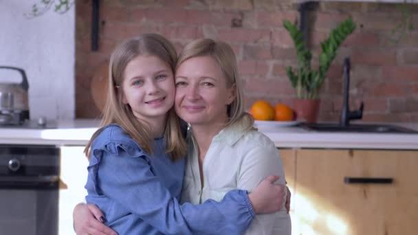 láska matka, portrét šťastné maminky s malou dceruškou objímající a polibky na tvář v kuchyni doma