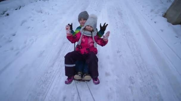 glückliche Kinder rodeln, Hand trägt Schlitten mit Jungen und Mädchen auf verschneiter Straße