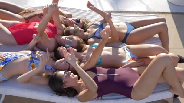 cheerful girlfriends into Swimsuit enjoy rest and wave hands lying on daybed on weekend