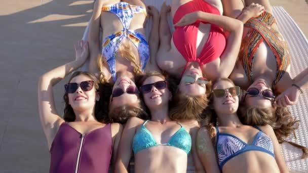 letní relax, společnost přítelkyň v plavkách a slunečních brýlích opalování na lehátku na dovolené