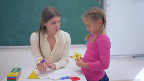 portrait of happy professional teacher female with smart schoolkid girl with plastic figures in hand near board in classroom of school