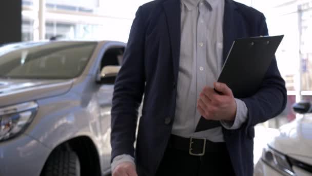 autó kereskedés, autó menedzser férfi tartja a kezében kulcsokat az új autó eladó bemutatóteremben
