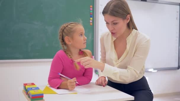 školní příprava, učitelka žena pomáhá studentce získat znalosti pomocí plastových figurek u stolu v blízkosti tabule ve třídě školy