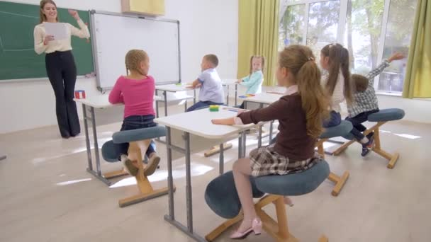 school lesson, young teacher near board conducts cognitive lesson for Smart children at desk in classroom of school