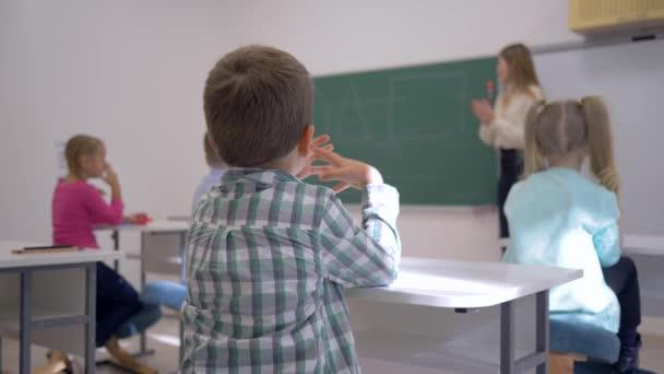 děti vyučování, školáci na lekci poslouchat pedagoga na tabuli v zaměřený ve třídě školy