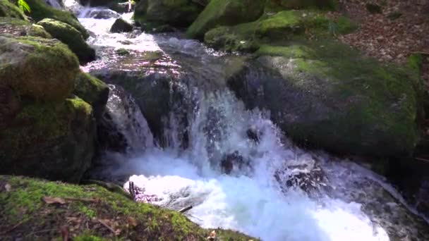 natural waterfall runs between large stones covered with green moss and makes splashes and foam in Slow motion