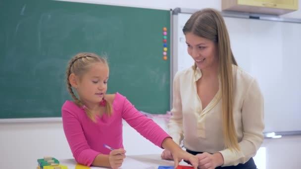 Individual education, Experienced tutor teaching smart girl at table near blackboard in classroom of School