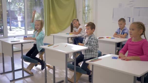 Kinder in der Schule, Jungen und Mädchen sitzen an Schreibtischen und heben während des Unterrichts in der Schule die Hände