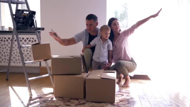 veselá rodina s malým synem si užívá nového světlého domova po opravách mezi kartonovými krabicemi s věcmi