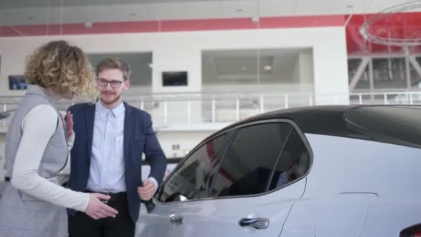 birthday surprise, husband gives new automobile gift to attractive wife with eyes closed which is emotionally happy at car dealership