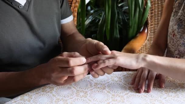 mens hands put gold wedding ring on feminine finger in cafe at table