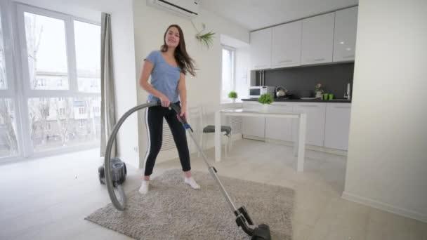 lustige Haushälterin beim Staubsaugen und viel Spaß beim Tanzen und Singen zu Hause im Zimmer
