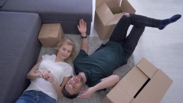 Heimwerker, glückliche schöne Mann und Frau liegen auf dem Boden zwischen Boxen und Planung des Zusammenlebens während der Erwärmung des Hauses in der neuen Wohnung