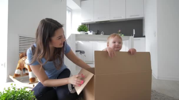 children entertainment, little cute baby in cardboard box playing hide-and-seek with mom and claps hand in room