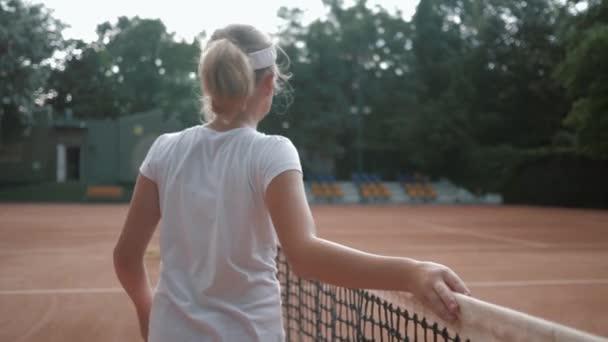 láska k tenisu, sportovní teenager dívka tenista s raketou dotýká sítě a procházky po hřišti po turnaji na čerstvém vzduchu