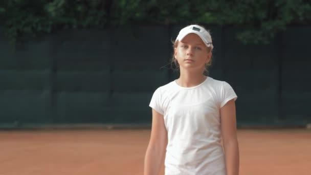 portrét profesionální tenista dívka s raketou do rukou na červeném hřišti venku