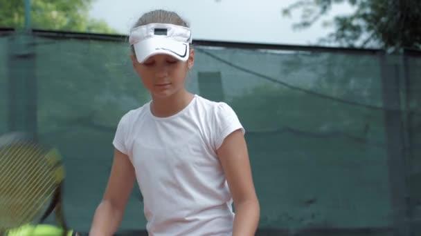 sportovní aktivity, roztomilé teen dívka tenista hity míč na zemi na hřišti a připraven na hru