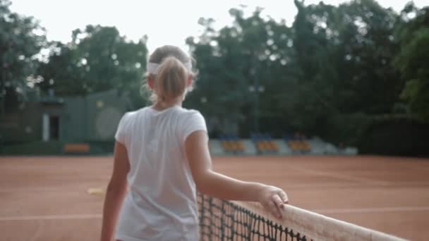 sportovní koníček, profesionální teen dívka tenista s raketou dotýká tenisové sítě a procházky po hřišti po mistrovství pod deštěm