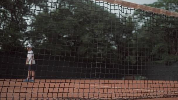 úspěšný tenisový zápas, sportovní radostný hráč kluk hity raketa na míči a běží až k síti s rukama nahoru a křičí štěstím na hřišti