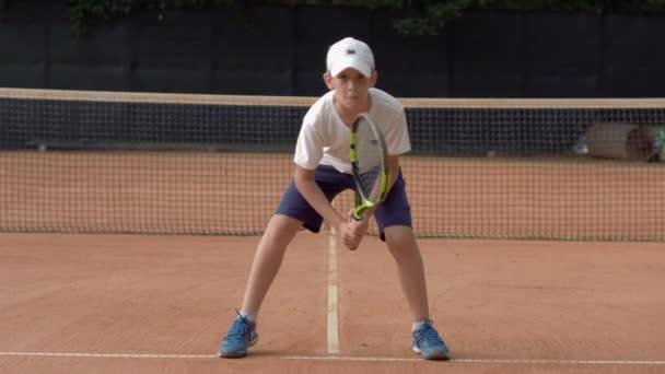 tenis trénink, cílevědomý dospívající chlapec trénink sloužit techniku s raketou bez míče na hřišti a připraven ke hře