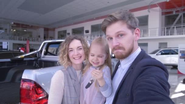 ügyfél pár aranyos gyermek lány kulcsok rekord videó a mobiltelefon közelében új vásárolt autó auto show