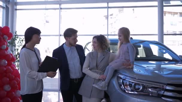 Auto business, happy purchases family with little daughter consulted with saleswoman about buying car at Auto sale center